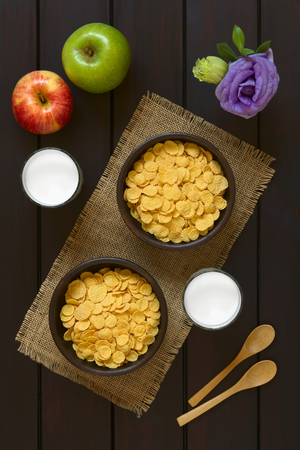 processed: Crispy corn flakes breakfast cereal in rustic bowls with glasses of milk, apples, wooden spoons and flower on the side, photographed overhead on dark wood with natural light Stock Photo