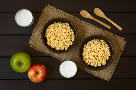 sweetened: Honey flavored breakfast cereal in two rustic bowls with glasses of milk, apples and wooden spoons on the side, photographed overhead on dark wood with natural light