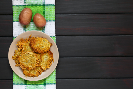 fritter: Homemade potato pancakes or fritters on plate, a traditional dish in Germany, photographed overhead on dark wood with natural light