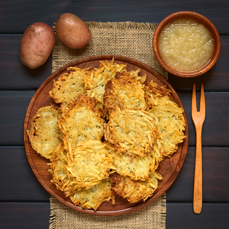 sauce dish: Homemade potato pancakes or fritters on wooden plate with apple sauce, a traditional dish in Germany, photographed overhead on dark wood with natural light
