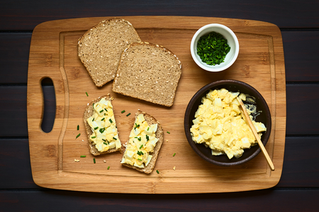 wholegrain mustard: Egg Salad Sandwich, fresh homemade egg salad prepared with mayonnaise and mustard on wholegrain bread sprinkled with chives, photographed overhead on dark wood with natural light