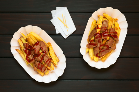 paper plates: Salchipapas made of French fries and fried sausage, a traditional fast food in South America, served with ketchup on paper plates, toothpick and napkin on the side, photographed overhead on dark wood with natural light