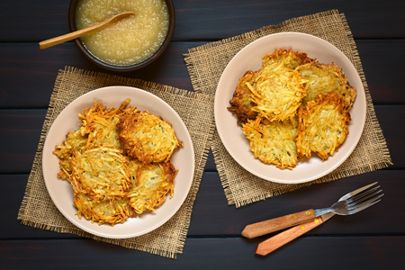 sauce dish: Homemade potato pancakes or fritters on plates with apple sauce, a traditional dish in Germany, photographed overhead on dark wood with natural light Stock Photo