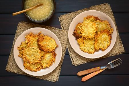 papas: Tortitas de patata caseras o buñuelos en platos con salsa de manzana, un plato tradicional en Alemania, fotografiado sobrecarga en madera oscura con luz natural Foto de archivo