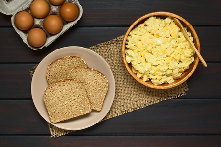 wholegrain mustard: Fresh homemade egg salad prepared with mayonnaise and mustard in wooden bowl, with slices of wholegrain bread on plate and eggs in carton, photographed overhead on dark wood with natural light