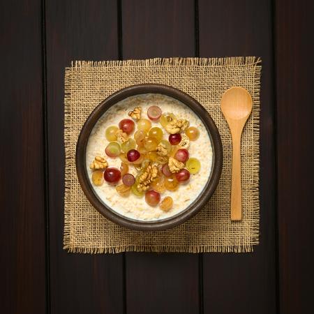 cereal: Gachas de harina de avena con uvas y nueces en cuenco rústico, cuchara de madera en el lado, fotografiado sobrecarga en madera oscura con luz natural