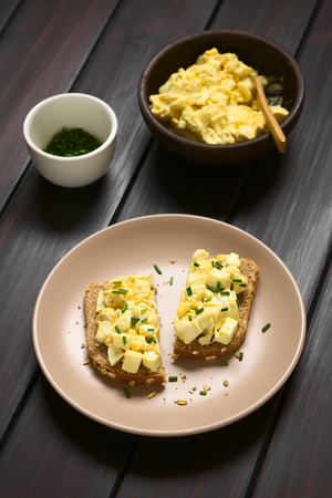 wholegrain mustard: Egg Salad Sandwich, fresh homemade egg salad prepared with mayonnaise and mustard on wholegrain bread sprinkled with chives, photographed on dark wood with natural light (Selective Focus, Focus on the front of the sandwiches)