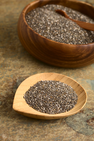hispanica: Chia seeds (lat. Salvia hispanica) on small bamboo plate, photographed on slate with natural light. Chia seeds are considered a superfood containing proteins, omega fats, minerals and antioxidants (Selective Focus, Focus one third into the chia on the pla Stock Photo