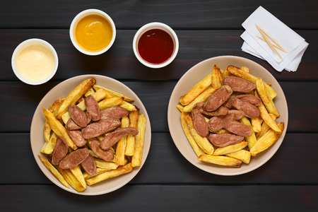 plates of food: Salchipapas made of French fries and fried sausage, a traditional fast food in South America, served on plates, mayonnaise, mustard, ketchup, toothpick and napkins above, photographed overhead on dark wood with natural light Stock Photo