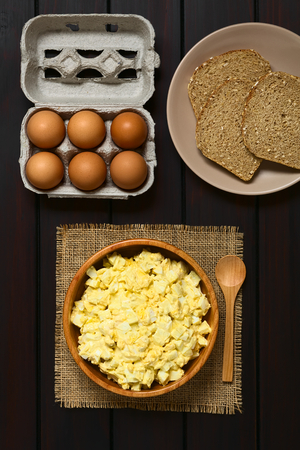 wholegrain mustard: Fresh homemade egg salad prepared with mayonnaise and mustard in wooden bowl, with egg carton and slices of wholegrain bread above, photographed overhead on dark wood with natural light