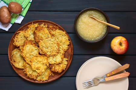 Homemade potato pancakes or fritters on wooden plate with apple sauce, a traditional dish in Germany, photographed overhead on dark wood with natural light
