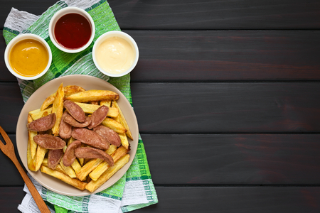 Salchipapas made of French fries and fried sausage, a traditional fast food in South America, served on plate, mayonnaise, ketchup, mustard and fork on the side, photographed overhead on dark wood with natural light