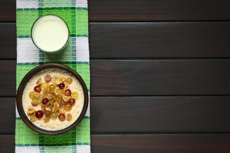 madera rústica: gachas de avena con uvas y nueces en cuenco rústico, vaso de leche arriba, fotografiado por encima en madera oscura con luz natural