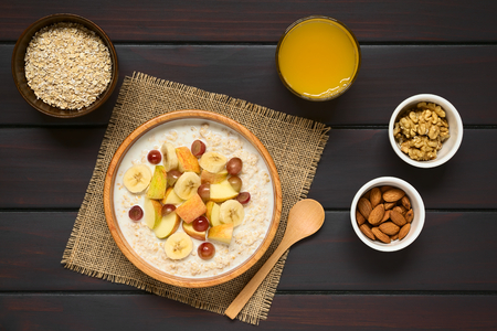 Oatmeal porridge with grape, apple and banana in wooden bowl, walnut, almond, raw oatmeal, fresh juice and wooden spoon on the side, photographed overhead on dark wood with natural light Stock Photo