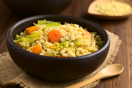 Vegan stew made of wheat grains, savoy cabbage, carrot, pumpkin and onion in rustic bowl, photographed on dark wood with natural light (Selective Focus, Focus on the carrot slice in the middle of the dish) Banco de Imagens