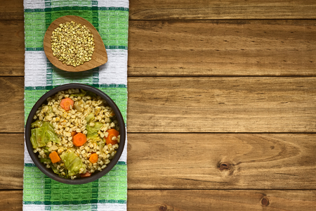 Vegan stew made of wheat grains, savoy cabbage, carrot, pumpkin and onion in rustic bowl, wheat grains on small plate above, photographed overhead on dark wood with natural light Banco de Imagens