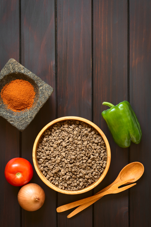 substitution: Raw textured vegetable or soy protein, called also soy meat in wooden bowl with raw vegetables and paprika in mortar. Photographed overhead on dark wood with natural light.