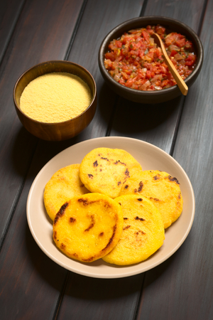 colombian: Plate of arepas with Colombian hogao sauce (tomato and onion cooked) and corn meal in the back. Arepas are made of yellow or white corn meal and are traditionally eaten in Colombia and Venezuela (Selective Focus, Focus on the first arepas)