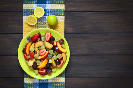 Overhead shot of fresh fruit salad made of grape, strawberry, plum and nectarine served on plate with lemon above, photographed on dark wood with natural light Foto de archivo