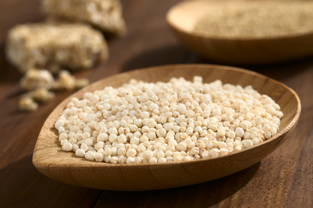 popped: Popped white quinoa (lat. Chenopodium quinoa) cereal on small wooden plate, raw quinoa grains and quinoa cereal bar in the back, photographed on wood with natural light (Selective Focus, Focus one third into the quinoa cereal)