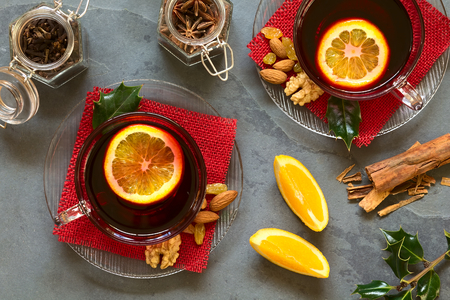 mulled wine spice: Mulled red wine with orange slice on top in glass cups. Mulling spices (cinnamon, cloves, star anise), orange wedges, nuts, almonds, sultanas on the side, photographed overhead on slate with natural light. Stock Photo