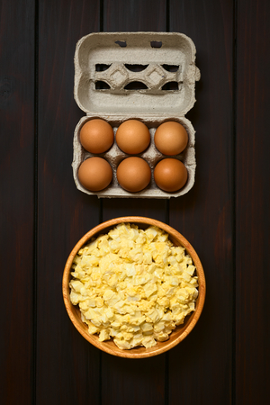 egg carton: Fresh homemade egg salad prepared with mayonnaise and mustard in wooden bowl, with egg carton above, photographed overhead on dark wood with natural light
