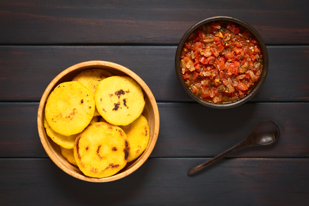 Overhead shot of arepas in wooden bowl with Colombian hogao sauce (tomato and onion cooked) and a spoon. Arepas are made of yellow or white corn meal and are traditionally eaten in Colombia and Venezuela. Photographed on dark wood with natural light.