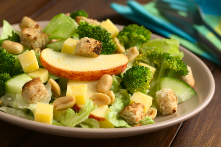Fresh vegetarian salad with apple, lettuce, broccoli, cucumber, peanut, cheese and homemade croutons on plate, photographed with natural light (Selective Focus, Focus on the front of the apple slice) Stock Photo