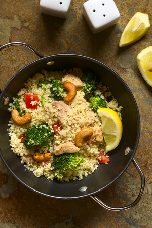 durum wheat semolina: Couscous dish with chicken, broccoli, tomato, cashew nuts. Lemon, salt and pepper shakers on the side, photographed overhead on slate with natural light.