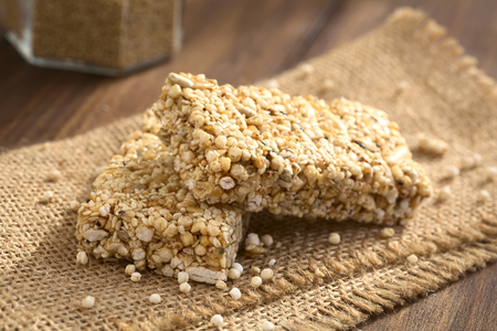cereal bar: Granola or cereal bars made of popped quinoa, sesame seed, popped rice, sunflower seed, chia and honey, photographed with natural light (Selective Focus, Focus on the front edge of the upper bar) Stock Photo