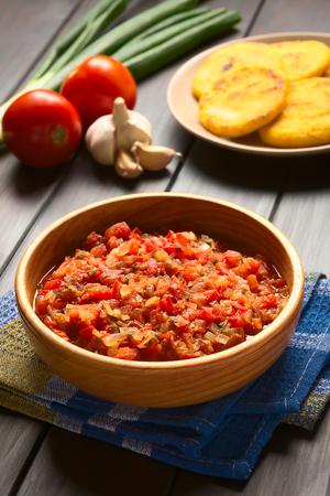 accompagnement: Hogao colombienne ou de la sauce cr�ole (salsa criolla) fait de l'oignon cuit et tomate, servi comme accompagnement des plats traditionnels, avec des ingr�dients et des arepas dans le dos, photographi� sur bois sombre avec la lumi�re naturelle (Mise au point s�lective, se concentrer au milieu de