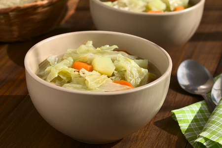 potato soup: Savoy cabbage, carrot and potato stew or thick soup in bowls, photographed on dark wood with natural light (Selective Focus, Focus in the middle of the first dish) Stock Photo