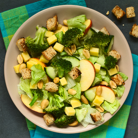 broccoli salad: Fresh vegetarian salad with apple, lettuce, broccoli, cucumber, peanut, cheese and homemade croutons on plate, photographed overhead with natural light (Selective Focus, Focus on the upper part of the salad)