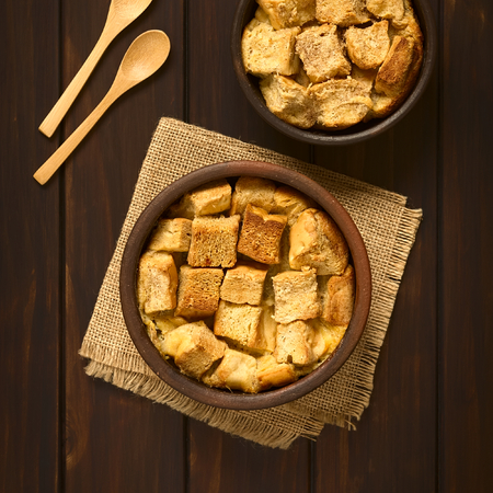 stale: Overhead shot of two rustic bowls of bread pudding made of diced stale bread, milk, egg, cinnamon, sugar and butter, photographed on dark wood with natural light