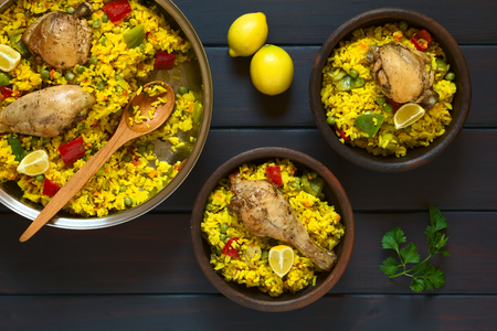 Overhead shot of two rustic bowls and a pot of chicken paella, a traditional Valencian (Spanish) rice dish made of rice, chicken, peas and capsicum and served with lemon, photographed on dark wood with natural light