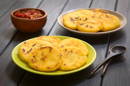 Two plates of arepas with Colombian hogao sauce (tomato and onion cooked) in the back. Arepas are made of yellow or white corn meal and are traditionally eaten in Colombia and Venezuela (Selective Focus, Focus on the first arepas) Stock Photo