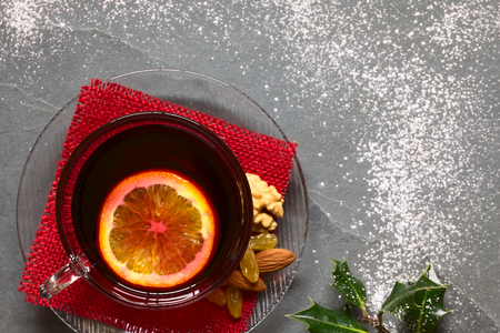 sugar powder: Mulled red wine with orange slice on top in glass cup, holly leaves on the side, slate surface sprinkled with sugar powder. Photographed overhead with natural light (Selective Focus, Focus on the mulled wine) Stock Photo