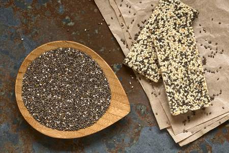 salvia hispanica: Chia seeds (lat. Salvia hispanica) on small bamboo plate with chia-sesame-honey granola bar on the side, photographed overhead on slate with natural light. Chia seeds are considered a superfood containing protein, omega fat, minerals, antioxidants.