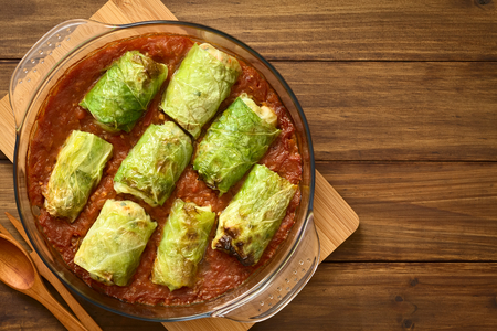 savoy cabbage: Vegetarian stuffed savoy cabbage rolls filled with wholegrain rice, pepper, onion and carrot, baked on tomato sauce in pan, photographed overhead on dark wood with natural light