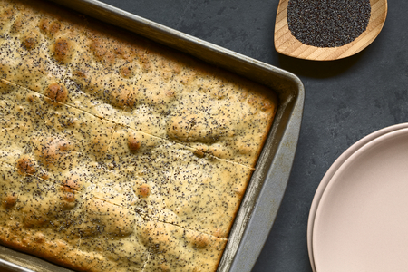 eggnog: Eggnog and poppy seed cake in baking pan. Poppy seeds and plates on the side, photographed overhead on slate with natural light. Stock Photo