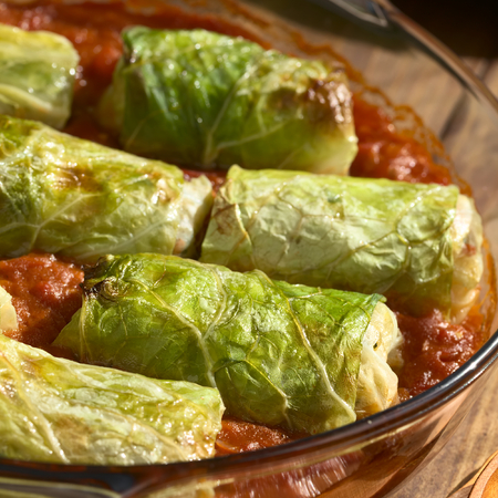 filled roll: Vegetarian stuffed savoy cabbage rolls filled with wholegrain rice, pepper, onion and carrot, baked on tomato sauce in pan, photographed with natural light (Selective Focus, Focus on the complete roll in the front) Stock Photo