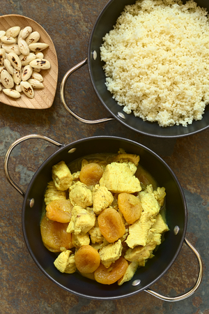 durum wheat semolina: Chicken and dried apricot stew, seasoned with turmeric, cinnamon and honey, accompanied by couscous, photographed overhead on slate with natural light