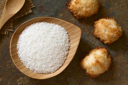 cocotier: Noix de coco râpée sur une petite plaque avec des macarons de noix de coco sur ardoise, photographié en tête avec la lumière naturelle (Mise au point sélective, Focus sur la noix de coco râpée et le haut des macarons)