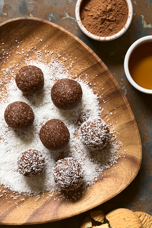 Coconut rum balls being covered with grated coconut on wooden plate, ingredients (cocoa powder, honey, cookies) on the side, photographed overhead on slate with natural light Standard-Bild