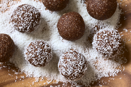 Coconut rum balls being covered with grated coconut on wooden plate, photographed overhead with natural light (Selective Focus, Focus on the top of the balls) Stockfoto