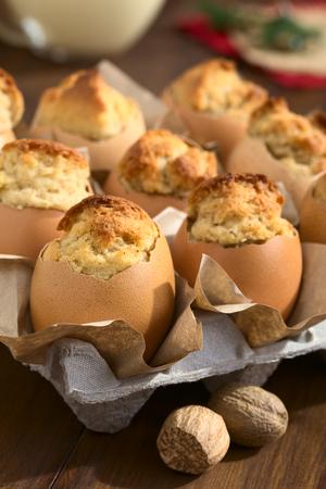 comida de navidad: bizcochos horneados ponche de huevo en cáscara de huevo, fotografiado con luz natural (enfoque selectivo, centrarse en la parte frontal de la primera magdalena)