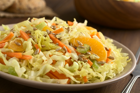 cabbages: Fresh salad made of savoy cabbage, carrot, celery, and orange with roasted sunflower seeds on top, photographed with natural light (Selective Focus, Focus one third into the salad)