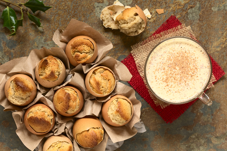 christmas spirit: Eggnog cupcakes baked in eggshell and eggnog drink in glass cup, photographed overhead with natural light (Selective Focus, Focus on the top of the cupcakes and the drink)