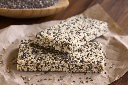 granola bar: Chia sesame honey granola bars, photographed with natural light. Chia (lat. Salvia hispanica)  is considered a superfood containing protein, omega fat, minerals, antioxidants (Selective Focus, Focus on the front edge of the granola bars)