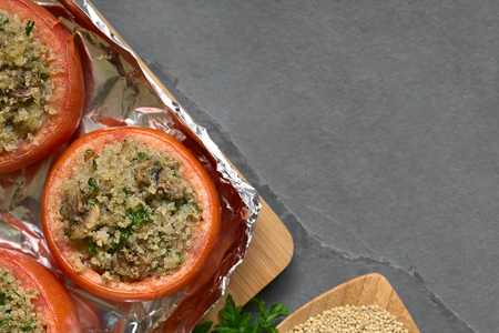 luz natural: Vegetarian baked tomato stuffed with quinoa, mushroom and parsley, photographed overhead  on slate with natural light